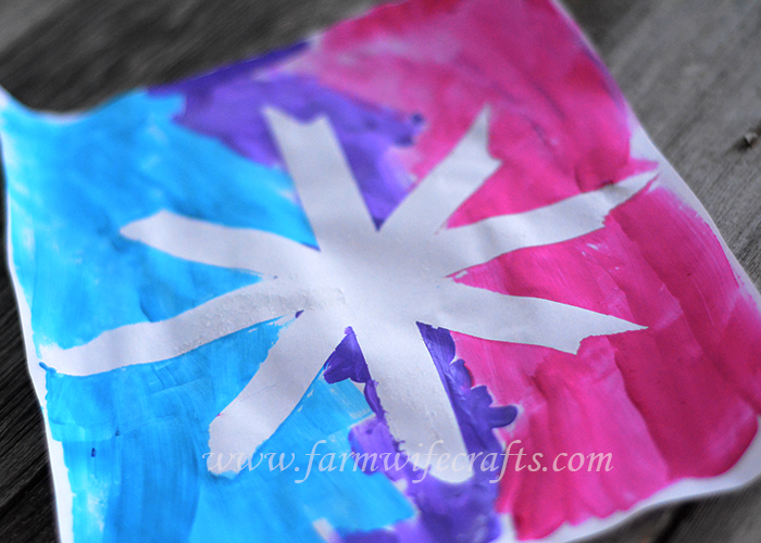 A simple craft to make with your toddler this winter are these snowflake paintings with masking tape.